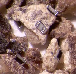 Габариты SMD-резисторов типоразмера 01005 в сравнении с частичками молотого чёрного перца
